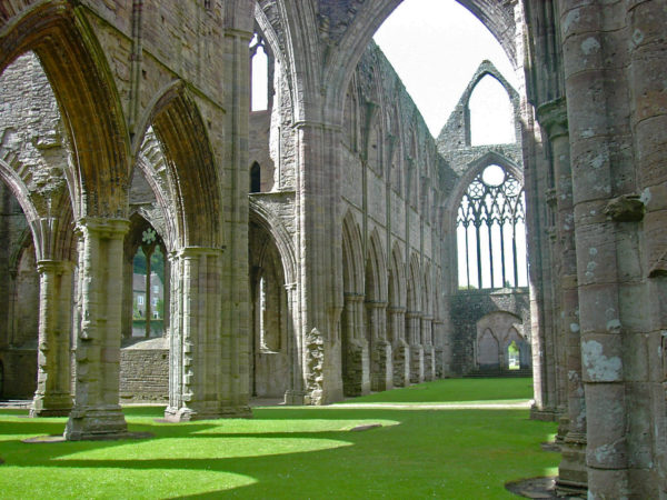 Photograph of the nave and stonework of Tintern Abbey, now in ruins, but with tall walls still standing with arched side chapels and spaces. The ground is a beautiful flat carpet of green grass.