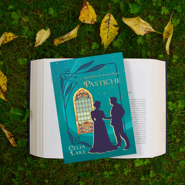 Copy of Pastiche on an open book on grass with yellow leaves. The cover has a silhouetted man and woman in Edwardian dress, in front of a golden stained glass window on a deep teal background.