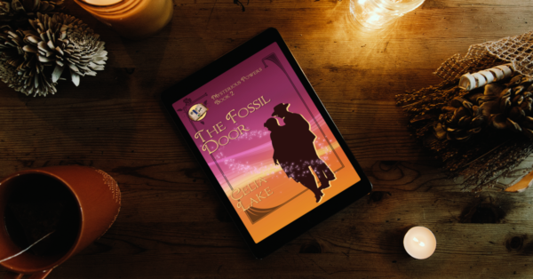 The Fossil Door cover displayed on an ereader, surrounded by candles, dried plants, and a mug of tea. The cover has a man and woman in silhouette at the right, looking to the left, on a background of dark burgundy to golden yellow, with an inset smaller image of an illuminated manuscript in the right corner.