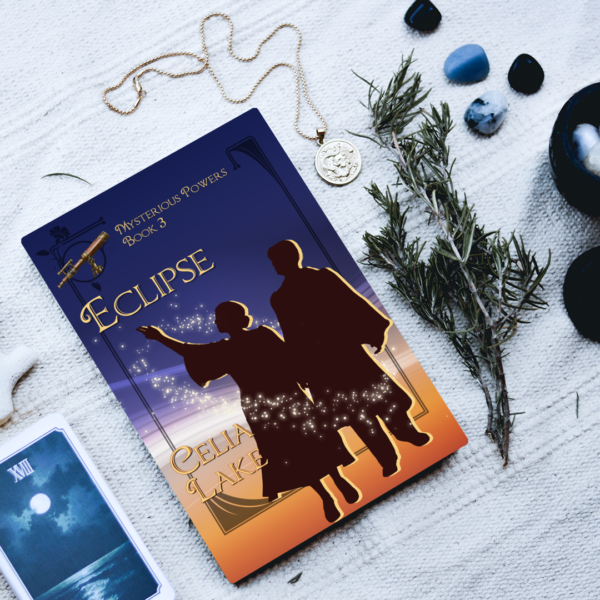 A copy of Eclipse surrounded by small items: a Tarot card showing the moon, a sprig of rosemary, a silver pendant, and several small stones. The cover has a man and woman, silhouetted in academic dress. The woman is gesturing up toward the sky. There is a telescope inset in the top left, and the cover is in shades of twilight blue and deep gold.